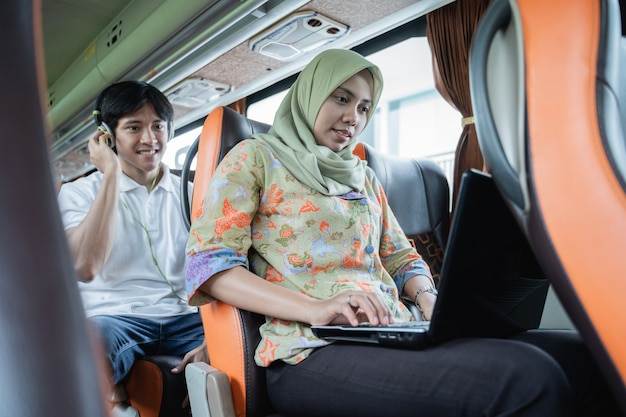 Uma mulher com véu usa um laptop enquanto um jovem está sentado atrás dela usando fones de ouvido enquanto está no ônibus