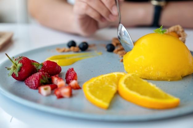 Uma mulher comendo bolo de laranja com uma mistura de frutas por colher em um café