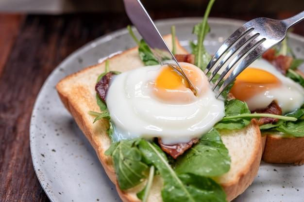 Uma mulher comendo sanduíche de café da manhã com ovos, bacon e creme de leite por faca e garfo em um prato na mesa de madeira