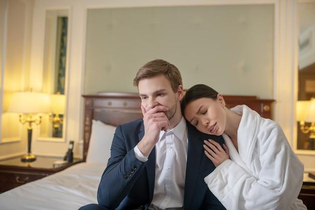 Uma mulher confortando um homem triste no quarto