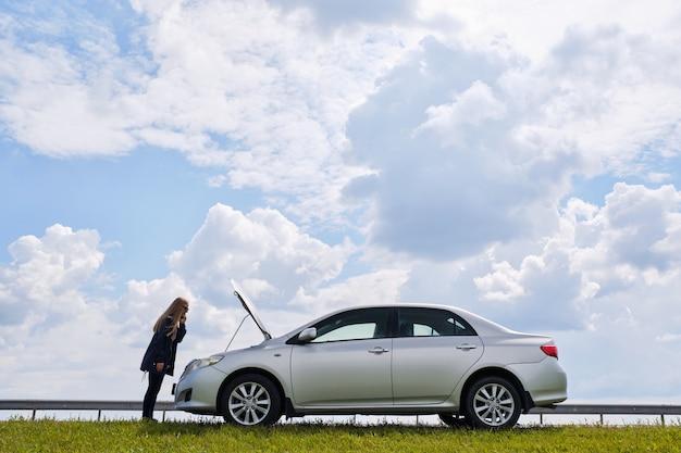 Uma mulher confusa espera por ajuda perto de um carro quebrado com o capô aberto, parado na beira da estrada