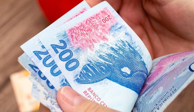 Uma mulher contando notas de dinheiro argentinas em uma foto de perto