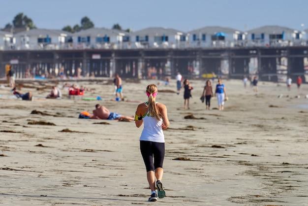 Uma mulher correndo na praia em san diego, eua