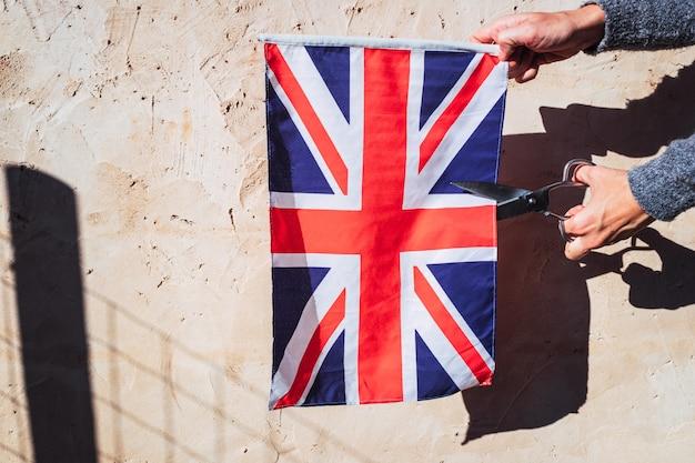 Uma mulher corta com tesoura a bandeira britânica em protesto.