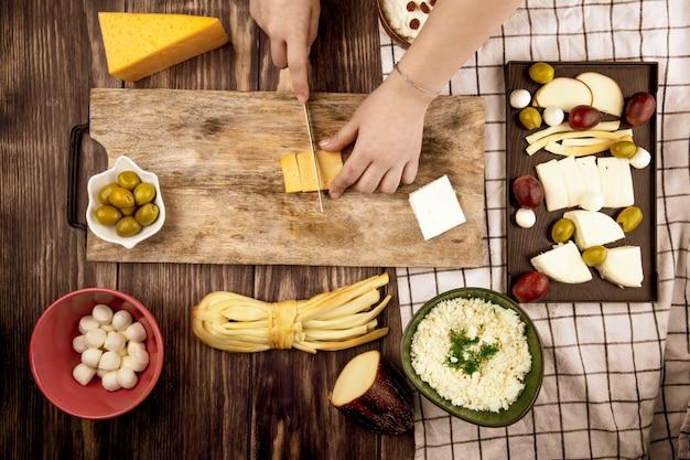 Uma mulher corta queijo holandês em uma tábua de madeira com azeitonas em conserva e vários tipos de queijo na vista superior rústica