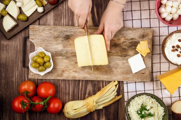 Uma mulher corta queijo holandês em uma tábua de madeira e azeitonas em conserva de tomates frescos na vista superior rústica