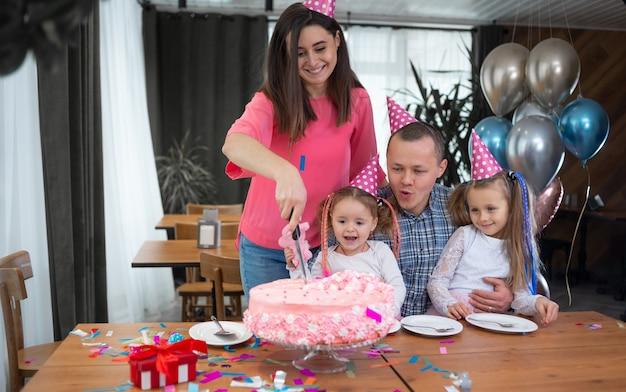 Uma mulher corta um grande bolo em pedaços. família e aniversário das crianças em casa. pais e filhas.