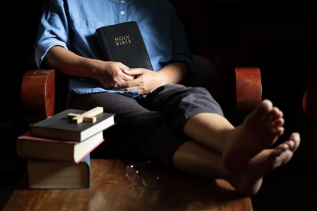 Uma mulher cristã sentada em uma cadeira de madeira