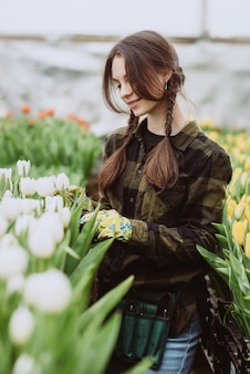 Uma mulher cuida de flores de tulipas no jardim. primavera e verão. jardineiro de mulher feliz com flores.