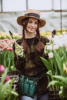 Uma mulher cuida de flores de tulipas no jardim