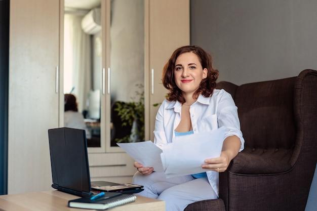 Uma mulher de 30 anos, com cabelos escuros e camisa branca, senta-se em uma poltrona em uma pequena mesa com um laptop, segura o papel nas mãos e trabalha remotamente em seu escritório em casa.