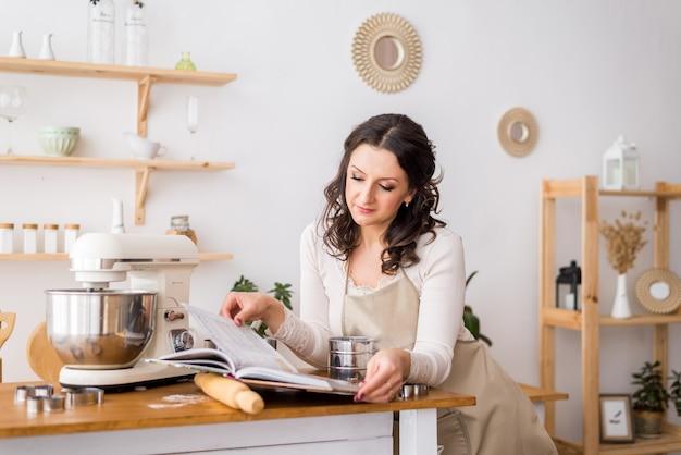 Uma mulher de avental lê um livro de receitas. preparando para cozinhar
