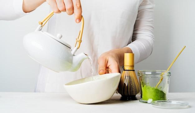 Uma mulher de branco derrama água de um bule para fazer chá verde orgânico japonês matcha