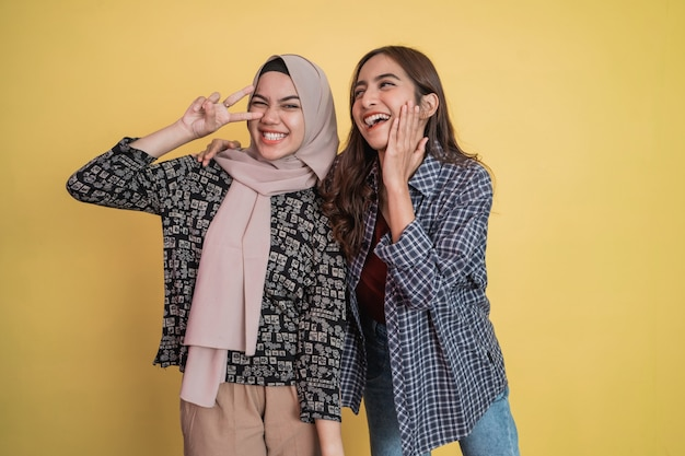 Uma mulher de cabelo comprido ri feliz e uma mulher com véu ao lado dela ri com gestos de ervilha ...
