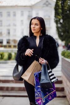 Uma mulher de cabelos castanhos, vestindo roupas pretas, segura sacolas de compras coloridas e estampadas durante uma maratona de compras bem-sucedida. caminhando lá fora, ela está curtindo o calor de um dia Foto gratuita