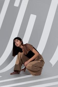 Uma mulher de calça bege está sentada no chão com as pernas abertas e uma sombra caindo em um brilhante