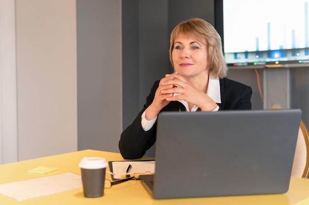 Uma mulher de camisa branca está treinando ouvintes na sala de negócios.
