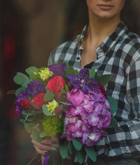 Uma mulher de camisa branca preta, segurando um buquê de flores misturadas na mão na rua