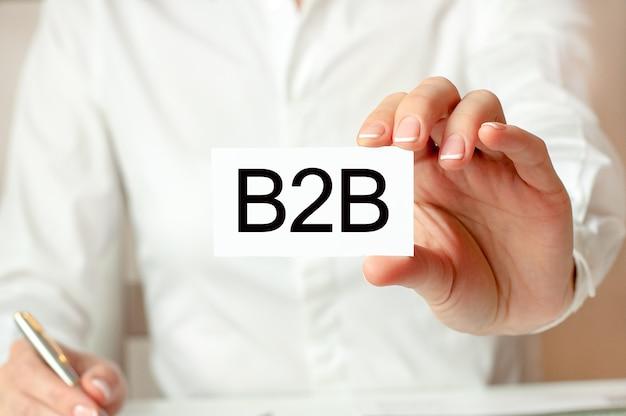 Uma mulher de camisa branca segura um pedaço de papel com o texto: b2b. conceito de negócio para empresas. b2b - abreviação de business-to-business.