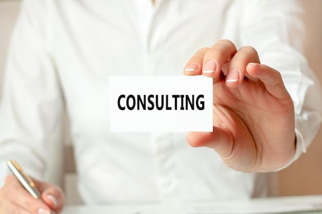 Uma mulher de camisa branca segura um pedaço de papel com o texto: consultoria. conceito de negócio para empresas.
