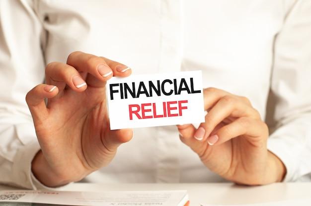 Uma mulher de camisa branca segura um pedaço de papel com o texto: relevo financeiro. conceito de negócio para empresas.