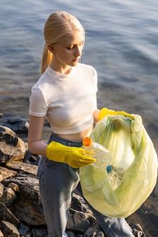 Uma mulher de camiseta branca e calça jeans segura um saco de lixo com garrafas de plástico vazias nas mãos. limpeza e limpeza do lago e de outros corpos d'água. respeito pela natureza.