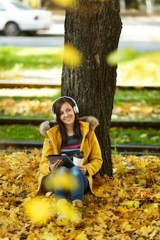 Uma mulher de casaco amarelo e calça jeans sentada com uma xícara de café ou chá e ouvindo música debaixo de uma árvore com um tablet nas mãos e fones de ouvido no outono parque da cidade em um dia quente. folhas de outono dourado.