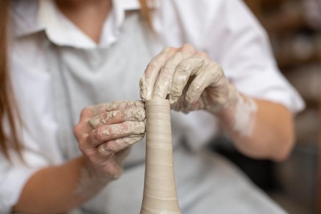 Uma mulher de ceramista trabalha com argila na roda de oleiro. a criação do vaso. oficina de cerâmica. fechar-se