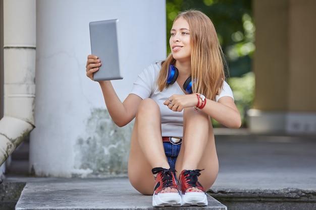 Uma mulher de cerca de 20 anos está usando um tablet pc para bater um papo com amigos enquanto está sentada na escada.