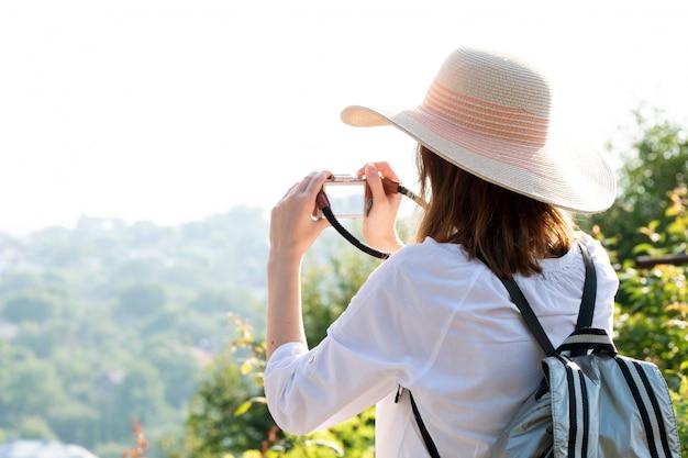 Uma mulher de chapéu, moletom branco e mochila viaja e tira fotos