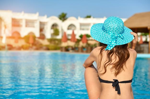 Uma mulher de chapéu, relaxando na luxuosa piscina de verão do hotel, o conceito de tempo para viajar.