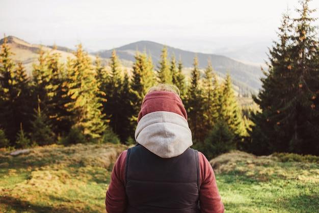 Uma mulher de close-up está de pé em uma jaqueta com capuz rosa e uma jaqueta sem mangas e está olhando para as montanhas.