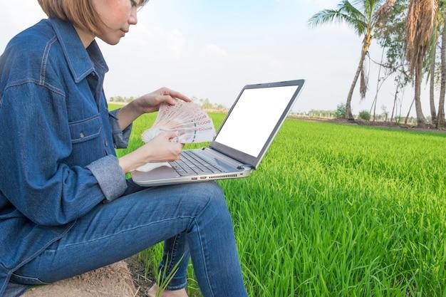 Uma mulher de fazendeiro sentada em um campo segurando notas e usando um computador portátil.