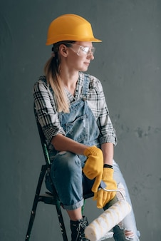 Uma mulher de força de vontade em um capacete de construção, luvas, óculos e macacão está envolvida em trabalhos de reparo e construção em casa. conceito de uma mulher forte e independente