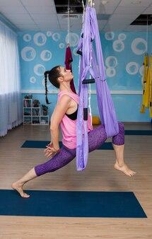 Uma mulher de ioga com roupas esportivas executa um asana em uma rede no estúdio