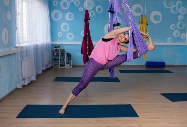 Uma mulher de ioga com roupas esportivas faz uma pose em uma rede no estúdio