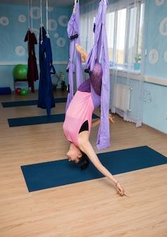 Uma mulher de ioga em roupas esportivas faz uma pose invertida em uma rede no estúdio