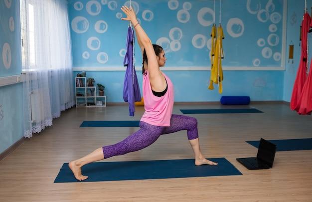 Uma mulher de ioga em roupas esportivas realiza exercícios à distância no estúdio