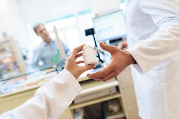 Uma mulher de jaleco branco dá ao homem uma garrafa de remédio.