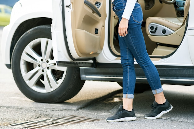 Uma mulher de jeans e tênis em pé perto de um grande carro todo-o-terreno ao ar livre. garota de motorista em roupas casuais fora de seu veículo.