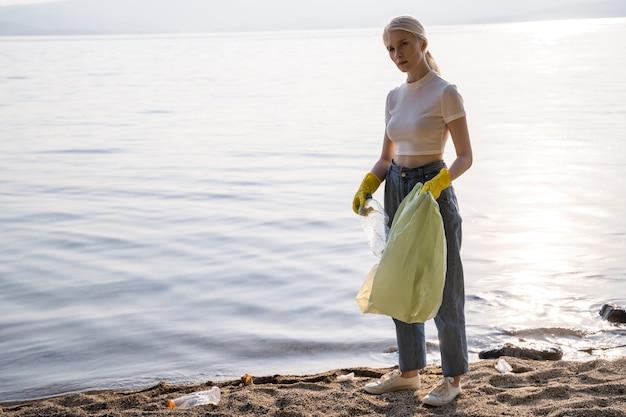 Uma mulher de luvas fica na margem do lago e olha para a câmera com aborrecimento. há muito lixo ao redor. atitude discreta em relação à natureza e ao meio ambiente.