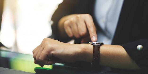 Uma mulher de negócios, apontando para um relógio de pulso em seu tempo de trabalho enquanto aguarda alguém no escritório