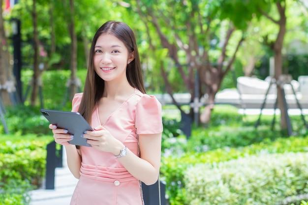 Uma mulher de negócios asiática profissional com cabelo comprido está sorrindo no jardim enquanto olha