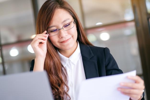 Uma mulher de negócios asiática usando e trabalhando em um laptop e a papelada no escritório