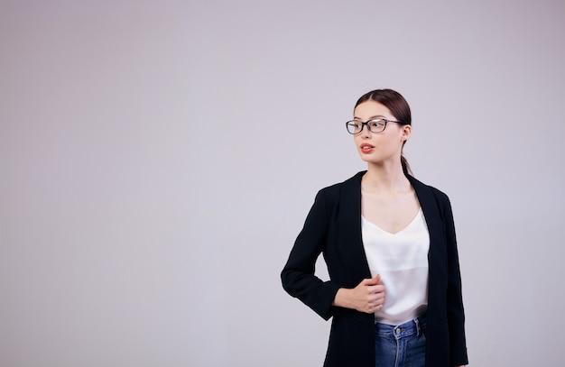 Uma mulher de negócios bonita está de pé em cinza em uma jaqueta preta, em uma camiseta branca e em óculos de computador. ocupado.