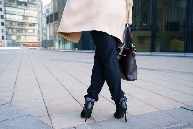 Uma mulher de negócios caminha de salto para o centro de negócios. foto horizontal conceitual sem rosto