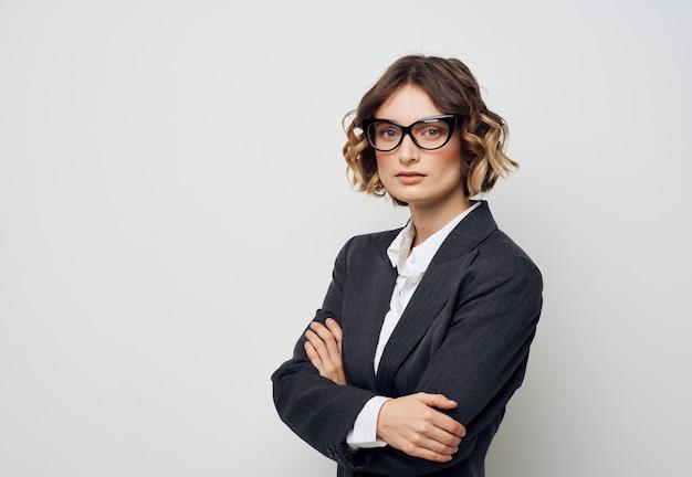 Uma mulher de negócios de óculos e terno em uma parede de luz cruzou os braços sobre o peito.