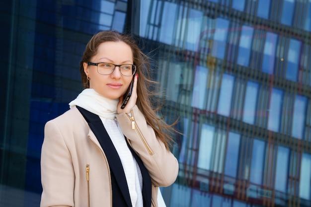 Uma mulher de negócios de óculos e terno está falando ao telefone no contexto de um prédio de vidro
