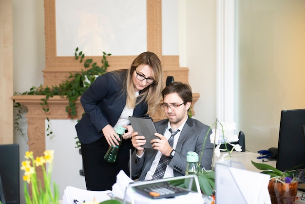Uma mulher de negócios e um jovem estão lendo um texto em um computador tablet em uma mesa no escritório