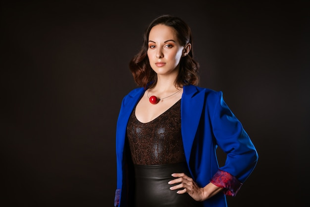 Uma mulher de negócios em um casaco azul posa para a câmera em um fundo escuro